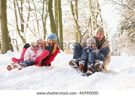Family Sledging Through Snowy Woodland - stock photo