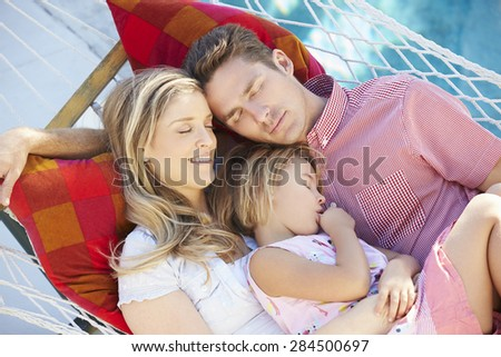 Family Sleeping In Garden Hammock Together - stock photo