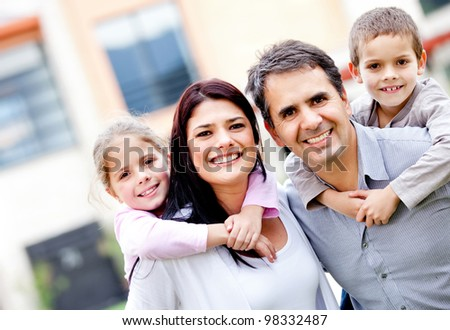 Family smiling and parents carrying kids outdoors - stock photo