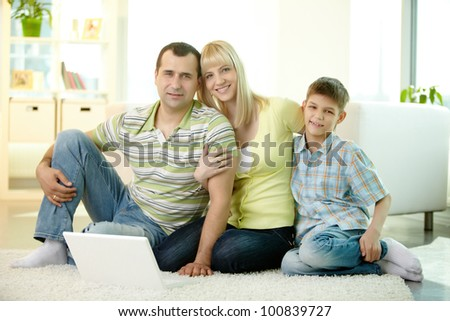 Family smiling at camera spending time at home together - stock photo