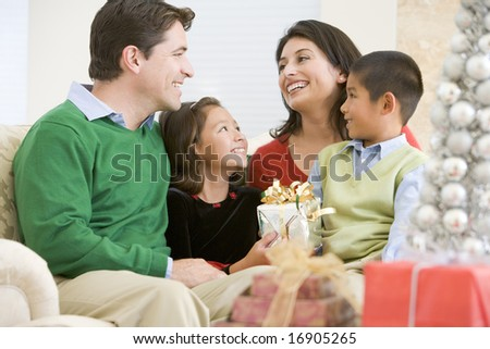 Family Smiling At Each Other,Holding Christmas Gift - stock photo