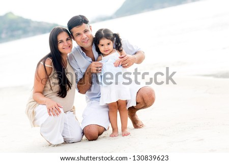 Family smiling at the beach enjoying their vacations - stock photo