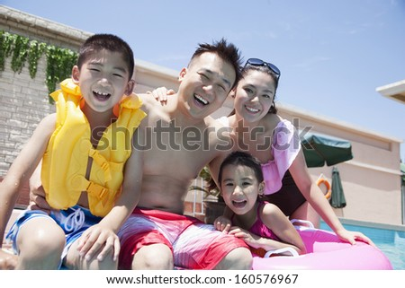 Family smiling by the pool - stock photo