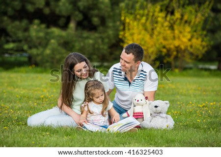 Family spending time together: parents reading book with their daughter - stock photo