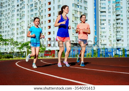 Family sport, happy active mother and kids jogging on track, running and working out on stadium in modern city  - stock photo