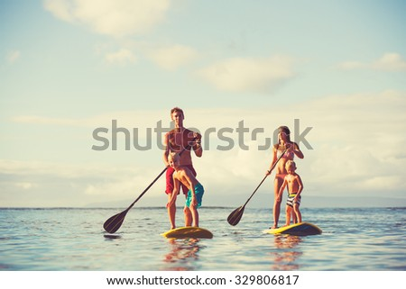 Family stand up paddling at sunrise, Summer fun outdoor lifestyle - stock photo