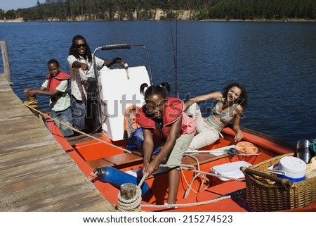 Family standing in motorboat beside lake jetty, girl tying rope to mooring post, smiling, portrait - stock photo