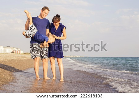 Family standing on a  sand seashore near sea playing in the water, relaxing on a vacation trip, looking on her husband. copy space - stock photo