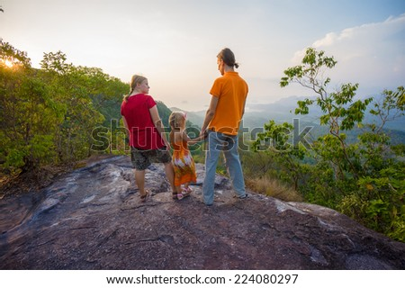Family stay near cliff on the top of tropical island mountain on sunset - stock photo