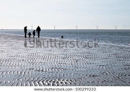 Family strolling on the beach - stock photo