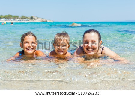 Family summer vacation - mother with her kids have fun and swimming in the transparent sea - stock photo