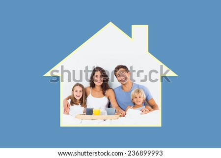 Family taking the breakfast on the bed against blue background with vignette - stock photo