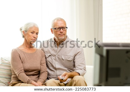 family, technology, age and people concept - senior couple watching tv at home - stock photo