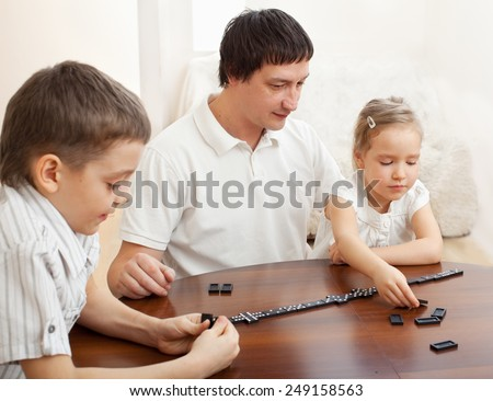 Family that plays dominoes. Father playing with children at home - stock photo