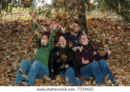family throwing leaves up in the air in autumn - stock photo