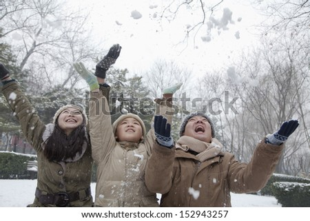 Family throwing snow into air in park - stock photo