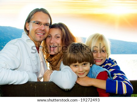family time - a cute family in the sunset - stock photo
