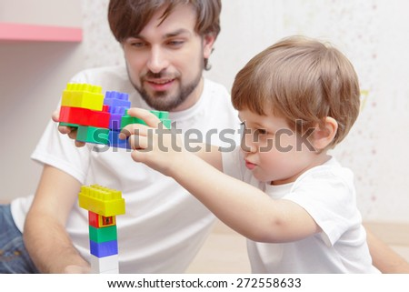 Family time. Close-up of a small boy joyfully playing with building bricks with his father - stock photo
