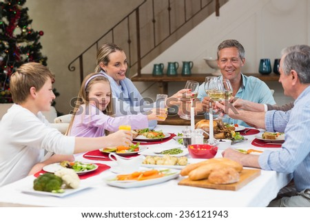 Family toasting with white wine in a christmas dinner at home in the living room - stock photo