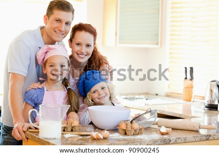 Family together with baking ingredients behind the kitchen counter - stock photo