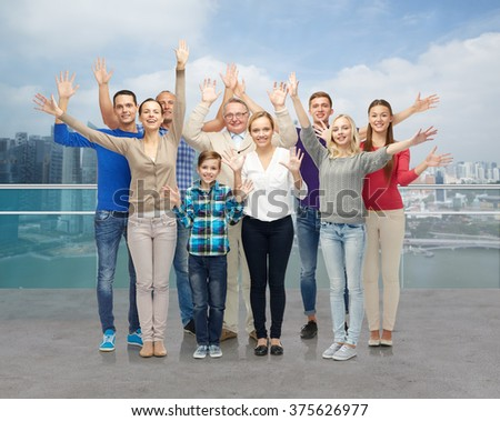 family, tourism, travel and people concept - group of smiling men, women and boy waving hands over singapore city waterside background - stock photo