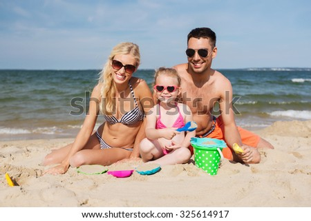family, travel, vacation and people concept - happy man, woman and little girl in sunglasses playing with sand toys on summer beach - stock photo