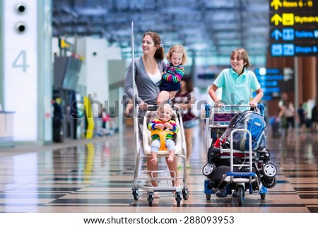 Family traveling with kids. Parents with children at international airport with luggage in a cart. Mother holding baby, toddler girl and boy flying by airplane. Travel with child for summer vacation. - stock photo