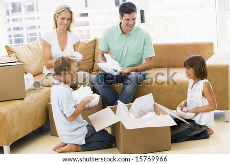 Family unpacking boxes in new home smiling - stock photo