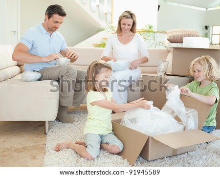 Family unpacking cardboard box together - stock photo