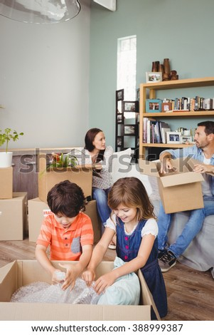 Family unpacking cardboard boxes in living room - stock photo