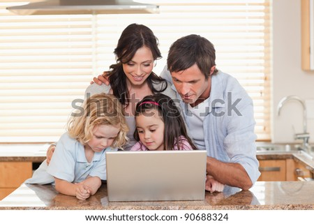 Family using a notebook together in a kitchen - stock photo