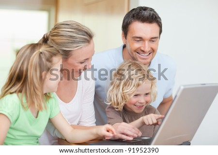 Family using notebook in the kitchen together - stock photo