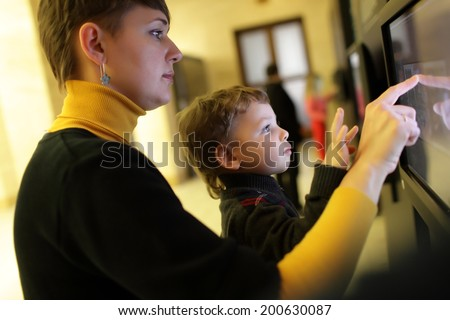 Family using touch screen in a museum - stock photo