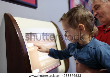 Family using touch screen in the museum - stock photo