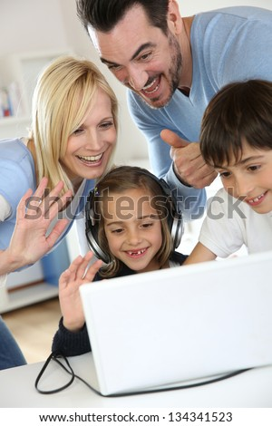 Family using webcamera to communicate with loved ones - stock photo