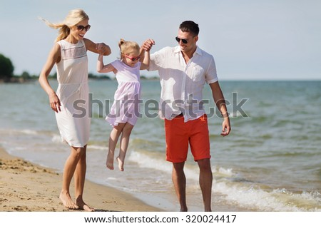 family, vacation, adoption and people concept - happy man, woman and little girl in sunglasses walking on summer beach - stock photo