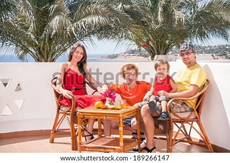 Family vacation. Caucasian happy family is sitting and laughing at the terrace with view on the sea. Relaxing family. Close up, outdoor (Sharm El Sheikh, Egypt).  - stock photo