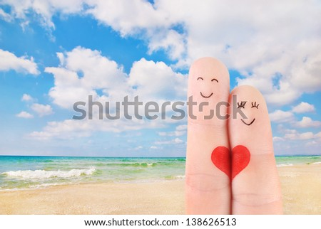 family vacation concept - a man and a woman hold on the red heart, painted at fingers against beautiful sea sand beach - stock photo