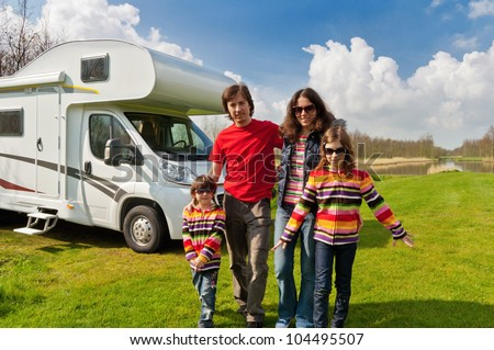 Family vacation in camping, camper trip. Happy active parents with kids travel on RV. Family having fun near their motorhome. Spring vacation trip with children. - stock photo