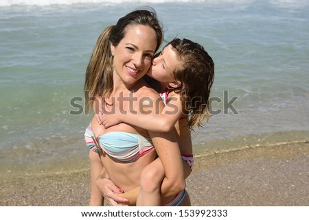 Family vacation on the beach: Child kissing mother  - stock photo