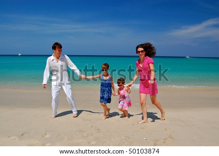 Family vacation. Parents with two children having fun on the tropical beach - stock photo