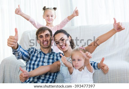Family values: portrait of happy american parents with little girls indoors - stock photo