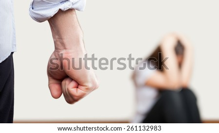 Family violence and aggression concept - furious angry man raised punishment fist over scared or terrified woman sitting at wall corner - stock photo