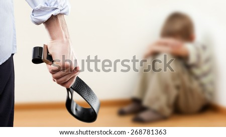 Family violence and aggression concept - furious angry man raised punishment hand holding leather belt over scared or terrified child boy sitting at wall corner - stock photo