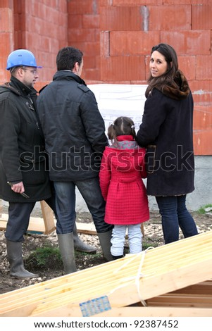 Family visiting unfinished new home - stock photo