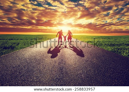 Family walk on long straight road, way towards sunset sun. Mother, father and child. Parenthood concepts - stock photo