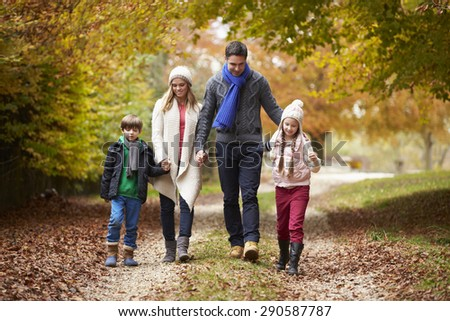 Family Walking Along Autumn Path - stock photo