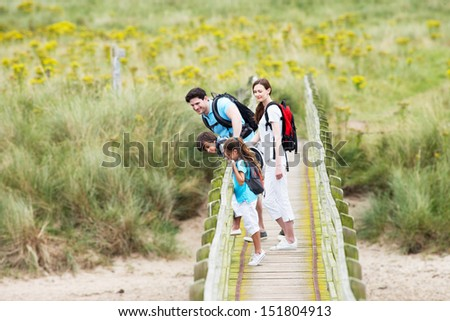Family Walking Along Wooden Bridge - stock photo