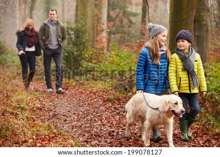 Family Walking Dog Through Winter Woodland - stock photo
