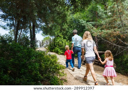 Family walking in the forest at summer time - stock photo